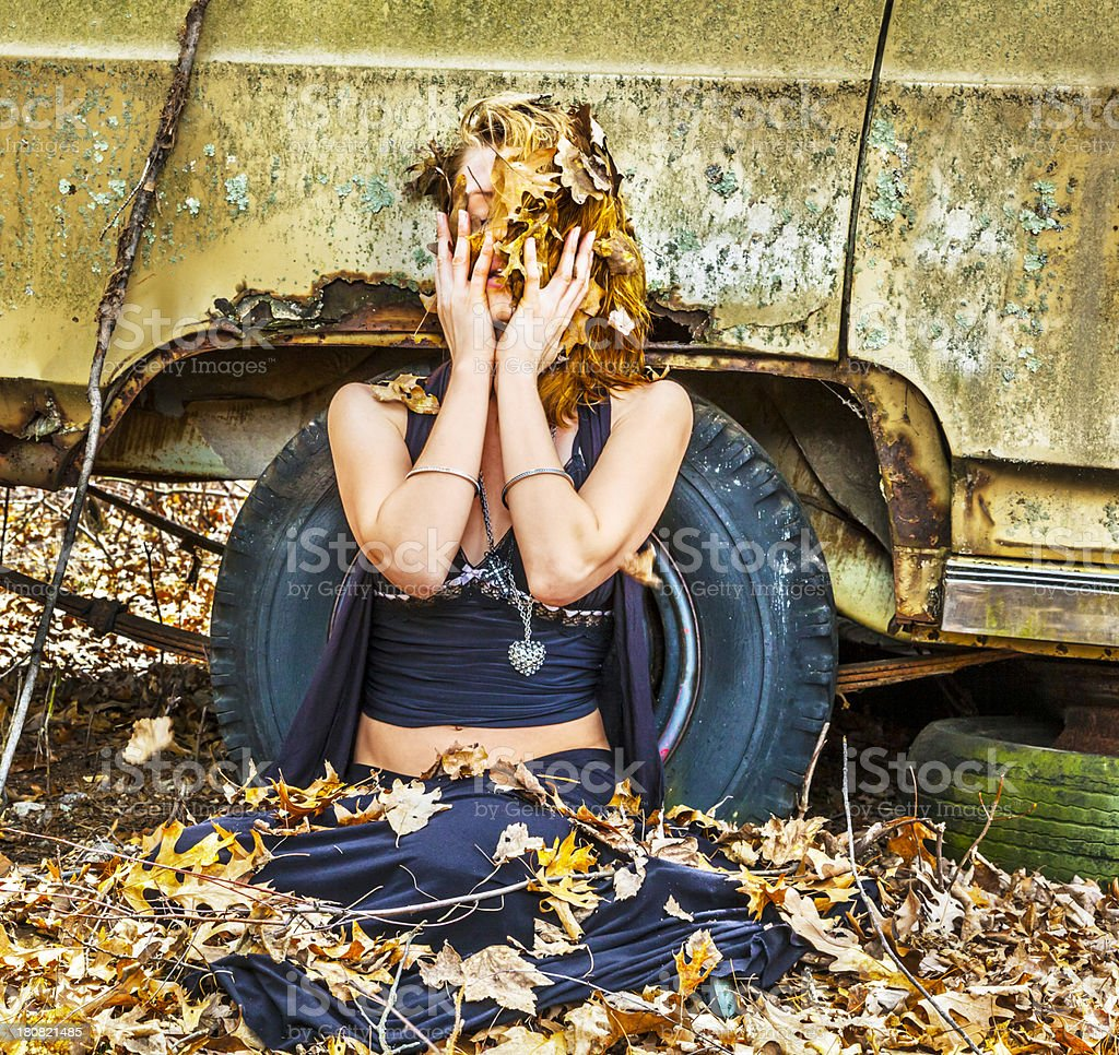 Woman Playfully Covering herself With Leaves stock photo