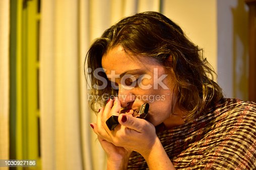 Middle-aged brunette woman playing a mouthpiece in a room