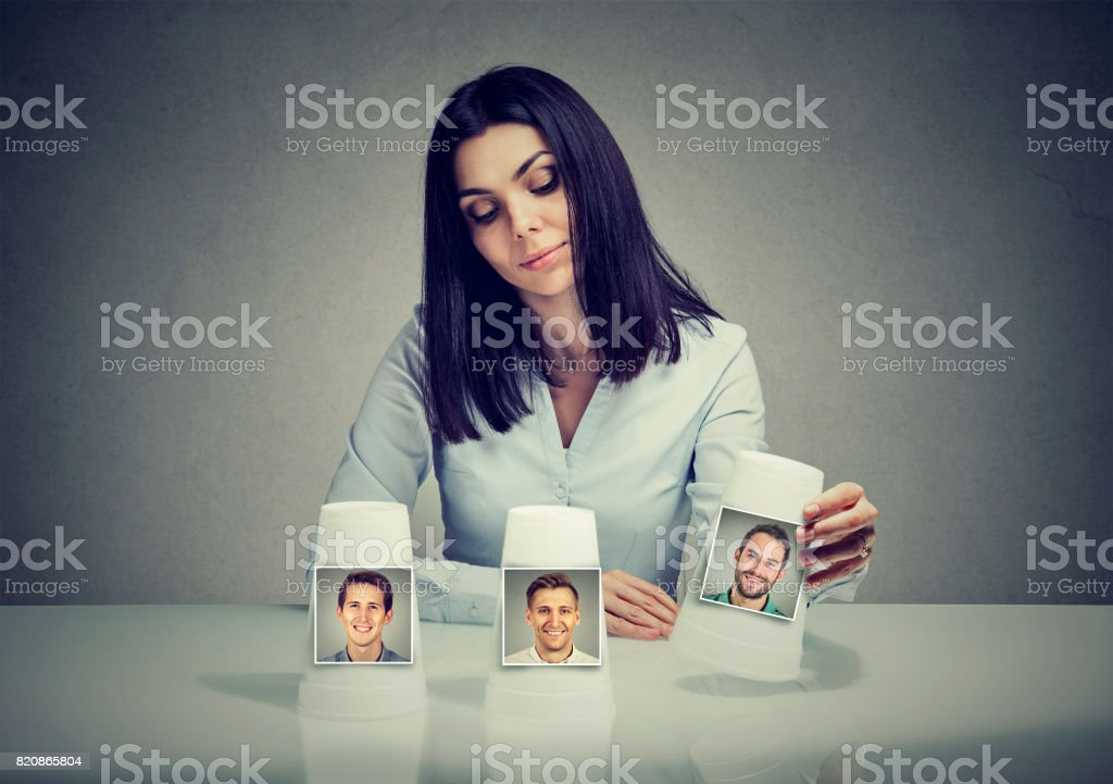 Woman playing a conjuring trick game making a boyfriend choice stock photo