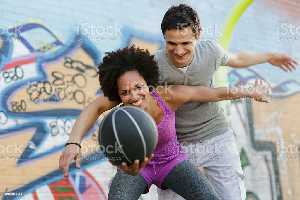 Woman Playing a Game of Basketball Against Man royalty-free stock photo