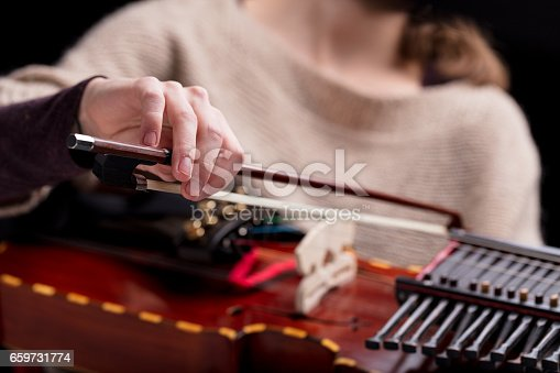 woman playing an ancient medieval musical instrument, modern reconstruction of an antique nyckelharpa, often used in folk or baroque musical concerts or dances