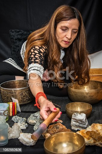 Woman playing a singing bowls also known as Tibetan Singing Bowls, Himalayan bowls. Tibetan Singing Bowls Treatment. Tibetan sound massage.