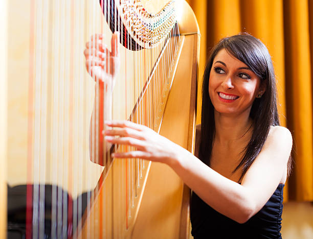 woman playing an harp - harpist stock photos and pictures