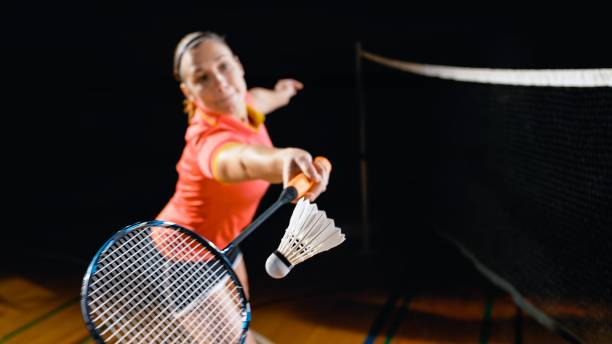 Woman playing badminton Young woman stretching to hit shuttlecock in badminton court. badminton stock pictures, royalty-free photos & images