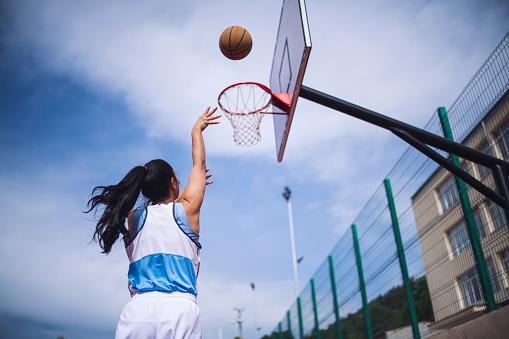 Rear view of woman aiming at basketball hoop.