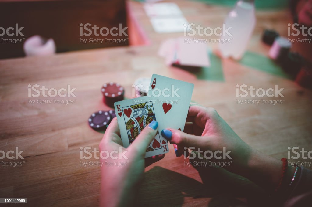 Woman playing cards and holding ace and king of hearts stock photo
