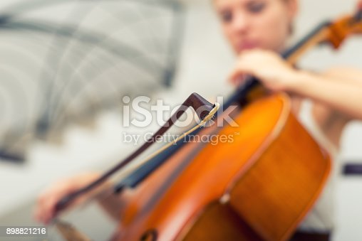 Young woman musician playing violoncello on the live concert.