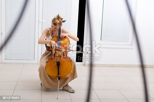 Young woman playing violoncello at home.