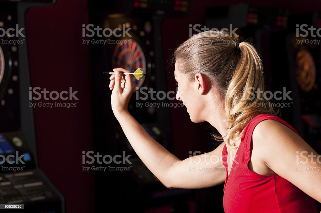 Woman playing darts in a red dress stock photo