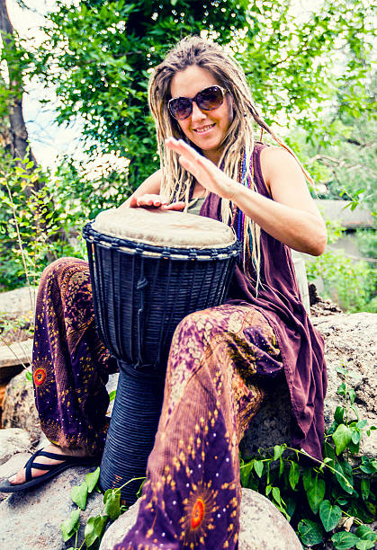 Woman Playing Djembe Drum Woman Playing Djembe Drum new age music stock pictures, royalty-free photos & images