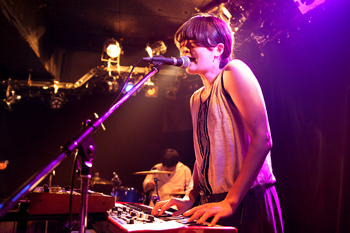 A young Japanese woman is playing an electronic keyboard while singing at a live event.