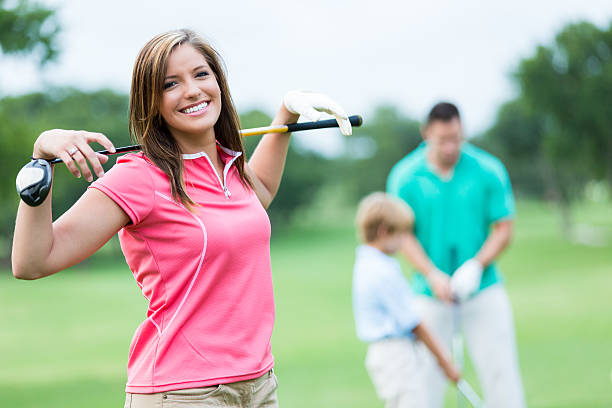 woman playing golf with family - female golfer stock photos and pictures