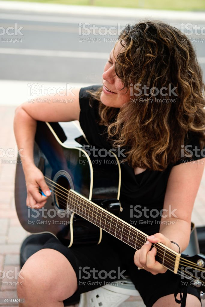 Woman playing guitar in family driveway. stock photo