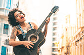 istock Woman playing guitar outdoors 1267230319
