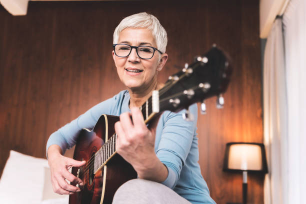 Woman playing guitar Portrait of beautiful mature woman playing guitar in cosy modern apartment, Free time hobbies music and art concept hobbies stock pictures, royalty-free photos & images
