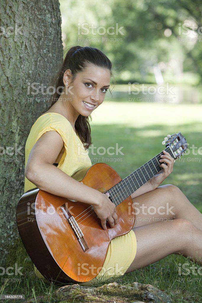 Woman playing guitar under a tree stock photo