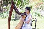 A Japanese female harpist is playing harp in a garden.