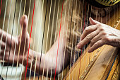 Woman playing harp with fingers on strings plucking
