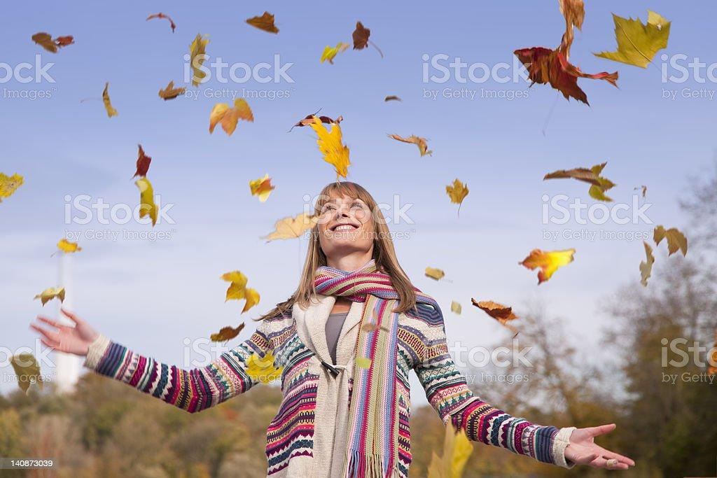Femme jouant avec des feuilles d'automne - Photo