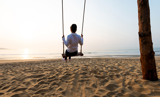 Woman playing on swing by the sea.