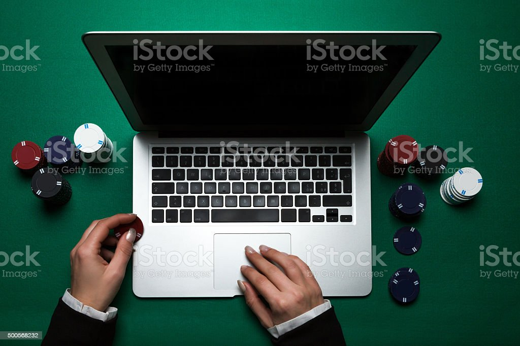 Woman playing online poker with laptop , top view stock photo