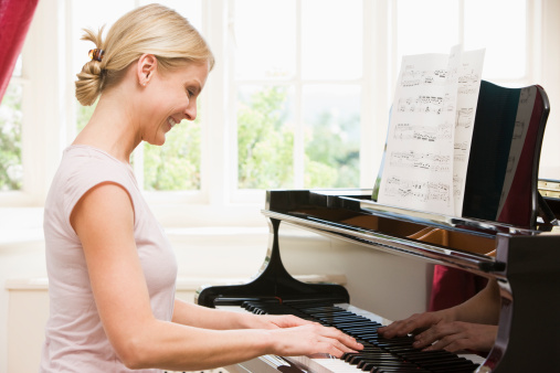 Woman playing piano and smiling