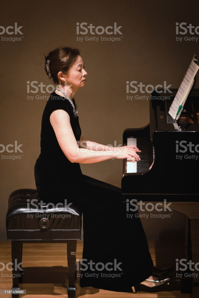 Woman playing piano at classical music concert