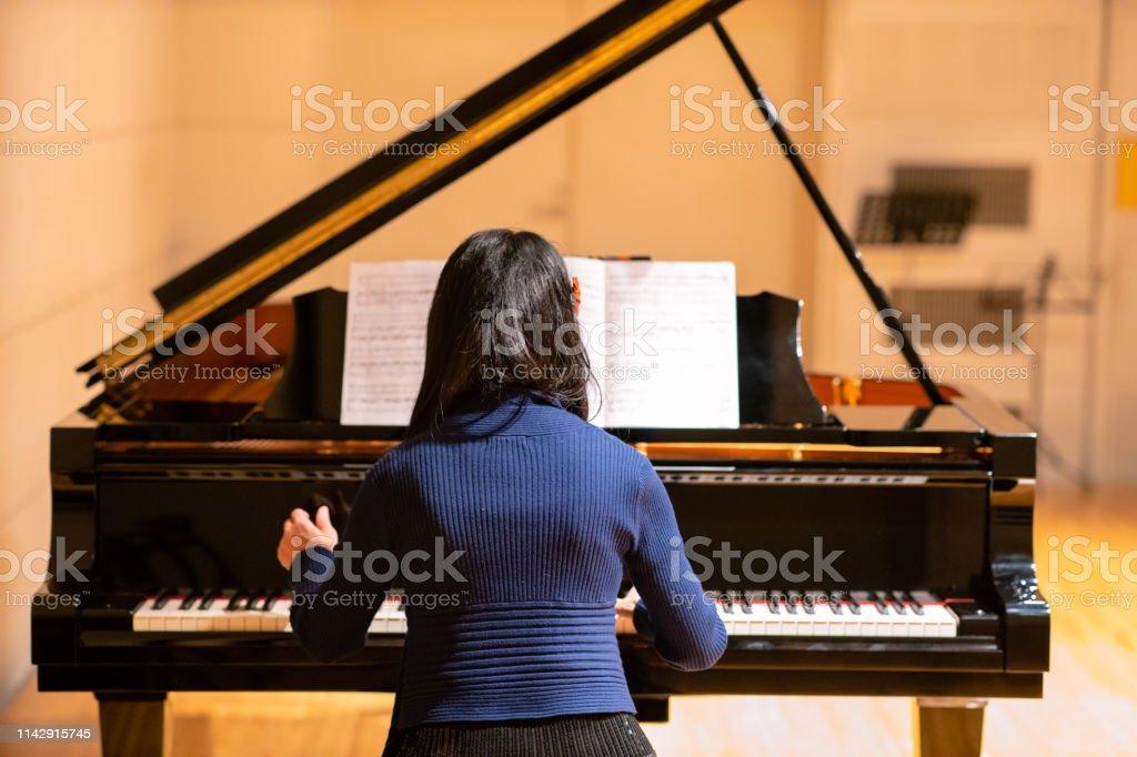 Woman playing piano at concert hall