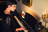 Young woman in old-fashioned black dress playing piano and drinking wine under candlelight in a romantic vintage room.