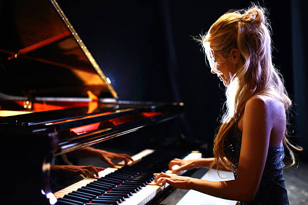 Woman playing piano in a concert. Side view of middle aged caucasian woman playing baby grand piano in a concert.She has long blond hair partially pulled back with a clip and shiny sleeveless dress. pianist stock pictures, royalty-free photos & images
