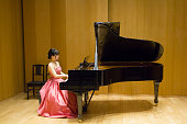 Side view of Japanese woman playing grand piano in a concert, rehearsal.