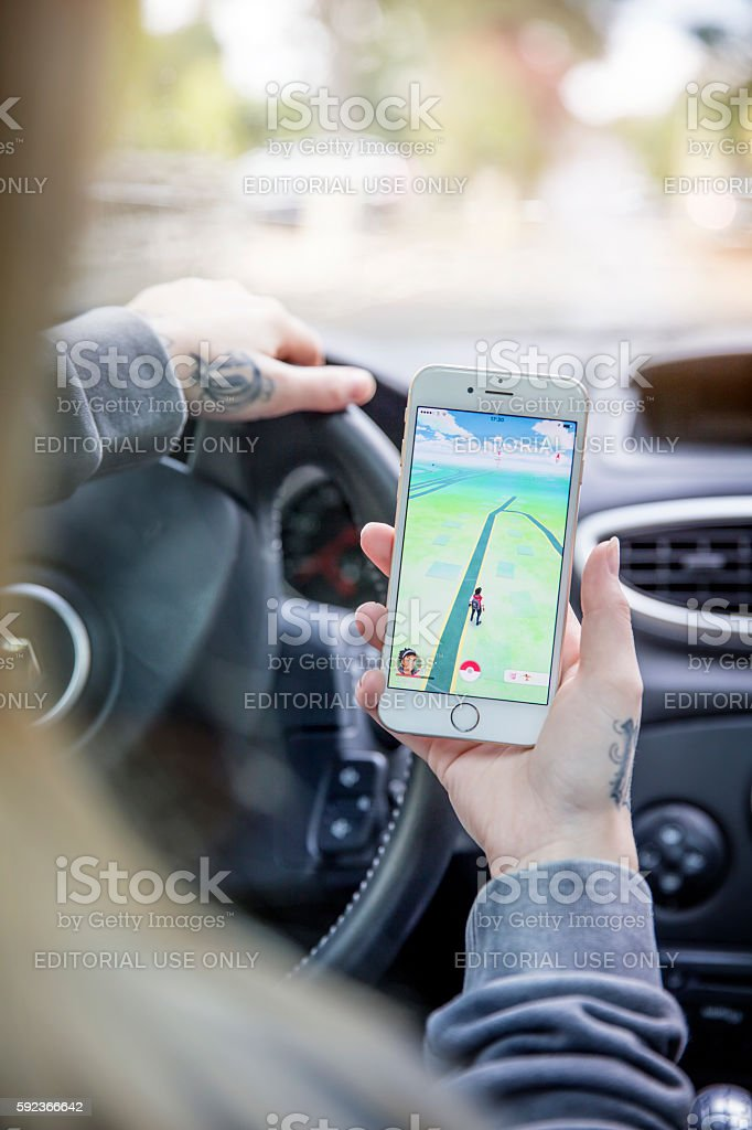 Woman Playing Pokemon GO in her Car stock photo