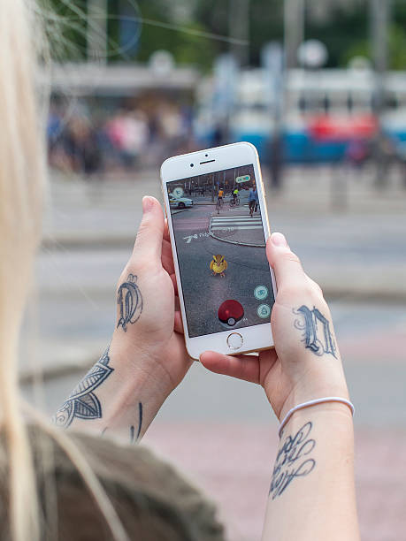 woman playing pokemon go on a cellpohne - mobile game stock photos and pictures