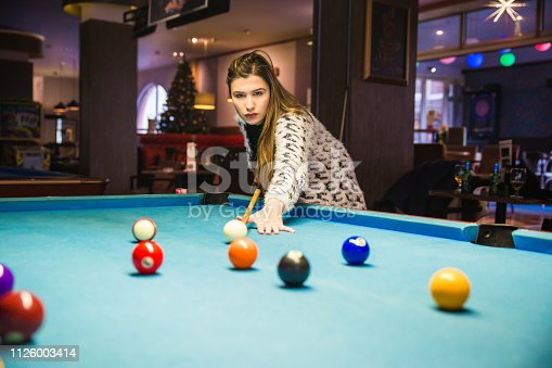Woman Playing Pool ready to hit Ball