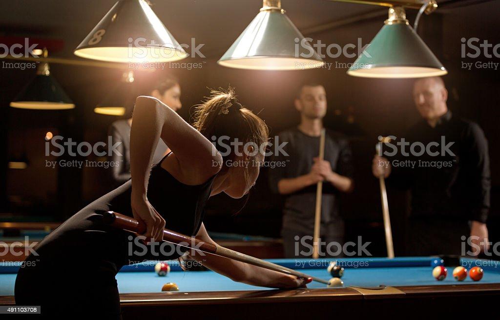 Femme jouant au billard avec un groupe d'amis - Photo