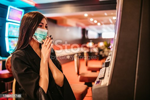 Beautiful young woman with protective face mask playing slot machine in casino.
