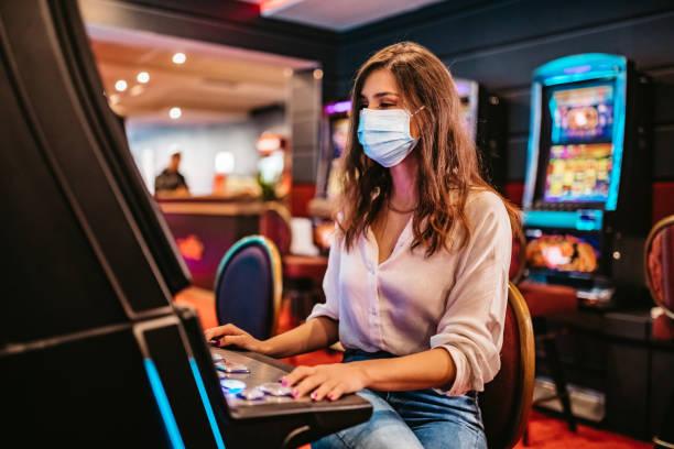 Woman playing slot machine in casino stock photo