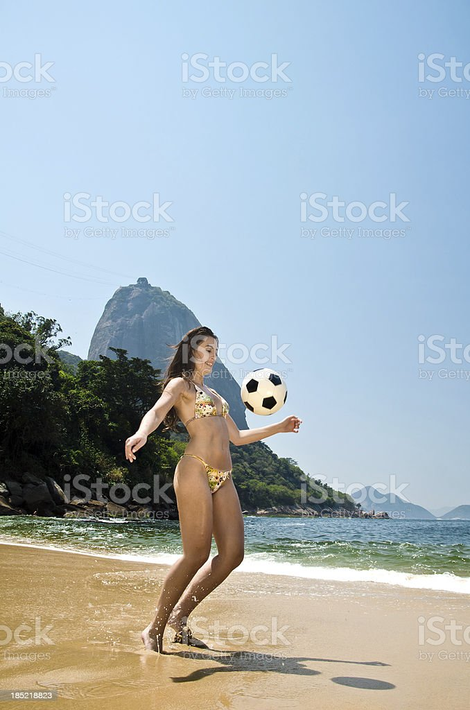 Woman playing soccer on beach stock photo