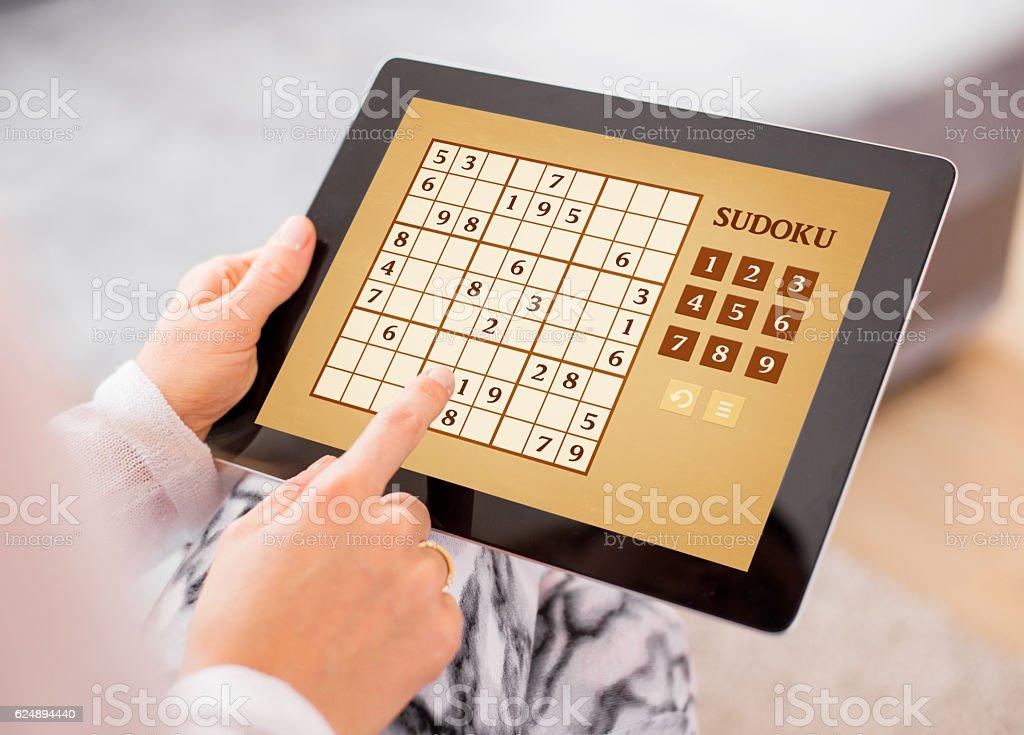 Woman playing Sudoku on tablet computer stock photo