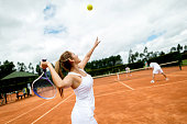 Woman playing doubles at tennis and serving