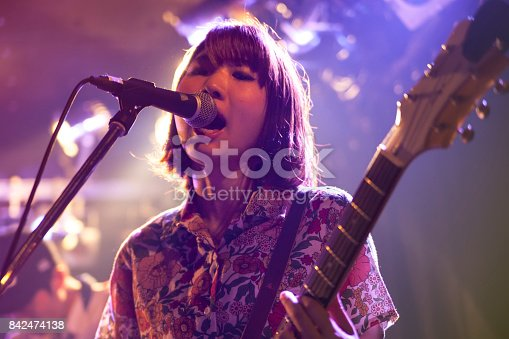 A young Japanese woman is playing the guitar during a live band event.