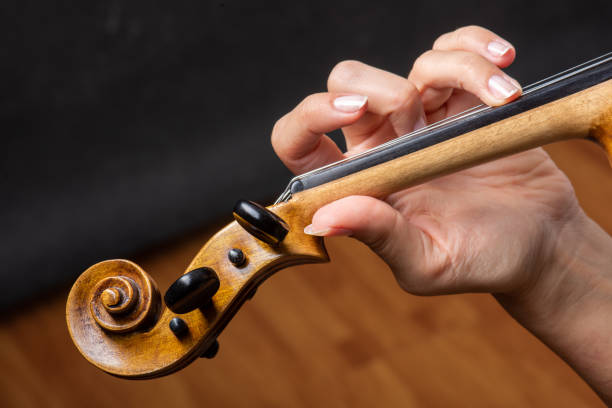 Woman playing the violin showing hands holding the bow stock photo
