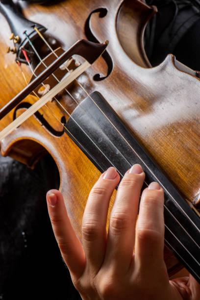 Kadın keman oynarken eller yay tutarak gösteren stok fotoğrafı
