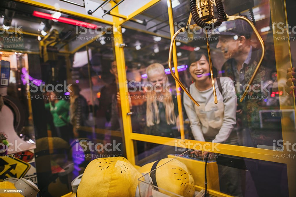 Woman playing toy grabbing game with friends stock photo