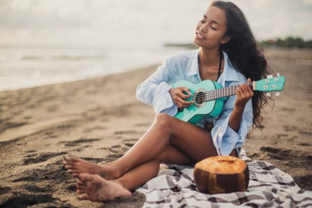 frau spielt ukulele am strand - ukulele songs stock-fotos und bilder