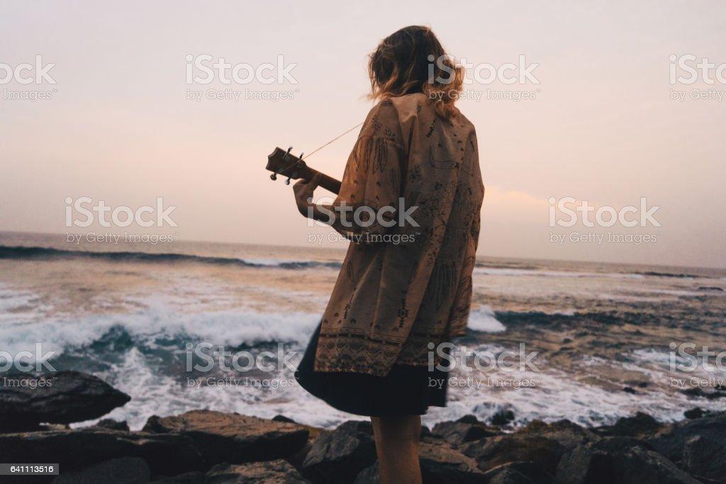 Woman playing ukulele near the sea stock photo
