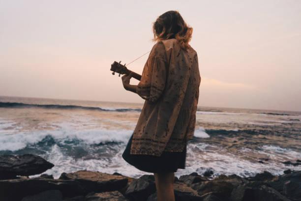 frau spielt ukulele nahe dem meer - ukulele songs stock-fotos und bilder