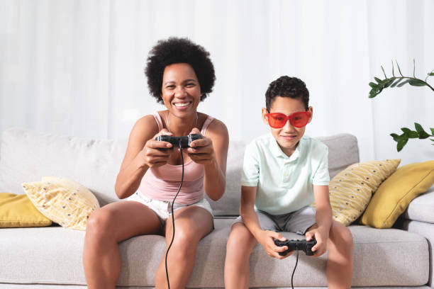 Woman playing video game with son stock photo
