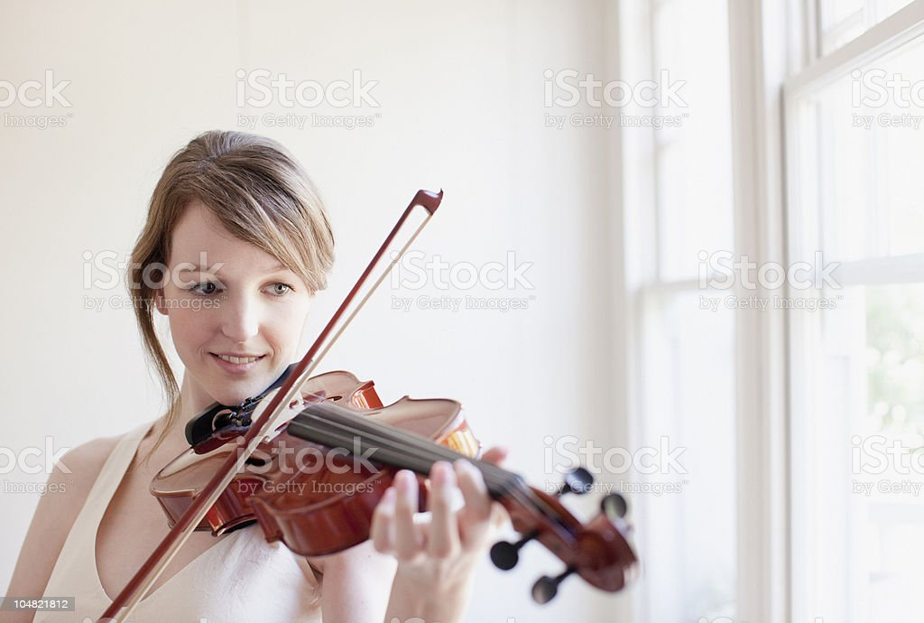 Woman playing violin near window stock photo