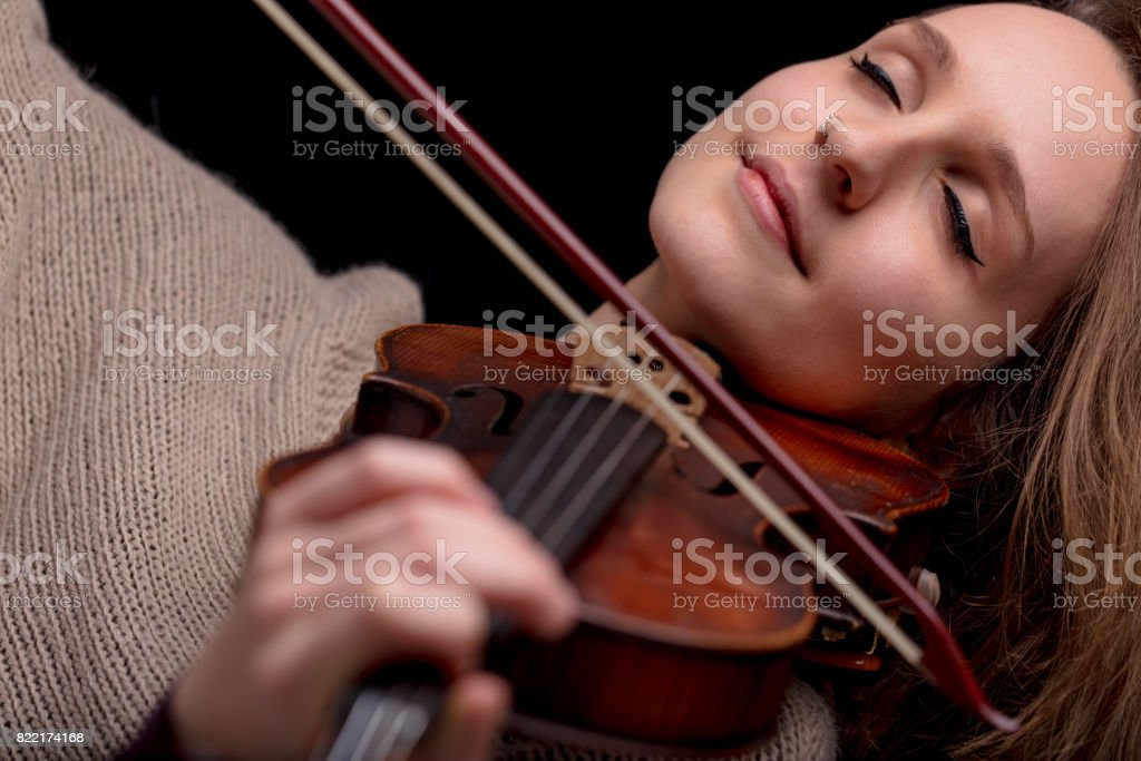 woman playing violin with her eyes closed stock photo